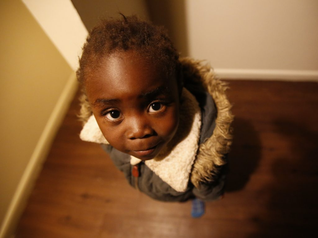 Moza Ausa, a 4-year-old refugee from the war-torn Democratic Republic of Congo, stands in the family's new apartment in Columbus, Ohio, in February.