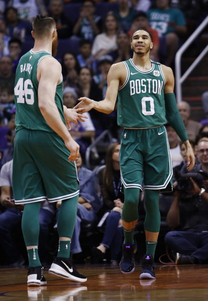 Celtics rookie Jayson Tatum, right, slaps hands with center Aron Baynes during the second half of Boston's 102-94 victory at Phoenix on Monday night. Tatum led Boston with 23 points. (AP Photo/Ross D. Franklin)