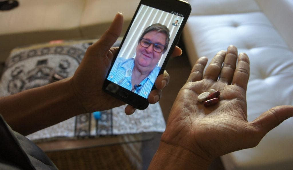 Public health nurse Peggy Cooley uses Skype video to remotely monitor a tuberculosis patient taking antibiotics at home in Lakewood, Wash.
