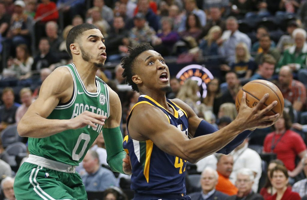 Jazz guard Donovan Mitchell drives to the basket as Celtics forward Jayson Tatum defends.