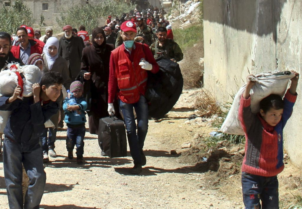 Carrying their belongings, civilians leave their homes in the eastern Ghouta region near Damascus, Syria, on Sunday.