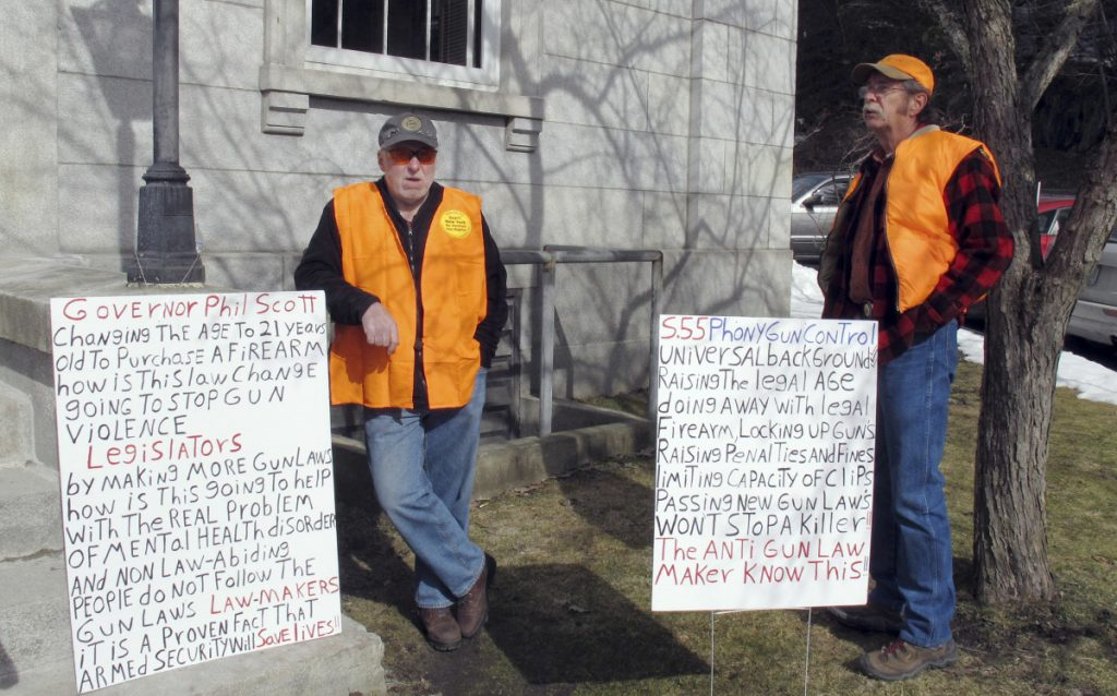 "Bert Saldi, left, of Barre, Vermont, stands with another protester who wouldn't give his name, outside the Vermont Statehouse on Tuesday in Montpelier, Vt. They were protesting a measure that would raise the legal age for gun purchases, expand background checks and ban high-capacity magazines and rapid-fire devices known as ""bump stocks."""