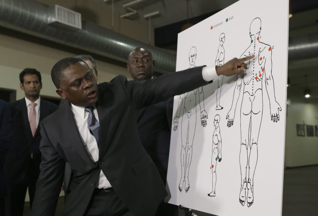 Dr. Bennet Omalu, a pathologist, points to a diagram showing the gunshot wounds he found on the body of police shooting victim Stephon Clark, during a news conference Friday in Sacramento, Calif. Omalu conducted an independent autopsy at the request of Clark's family.