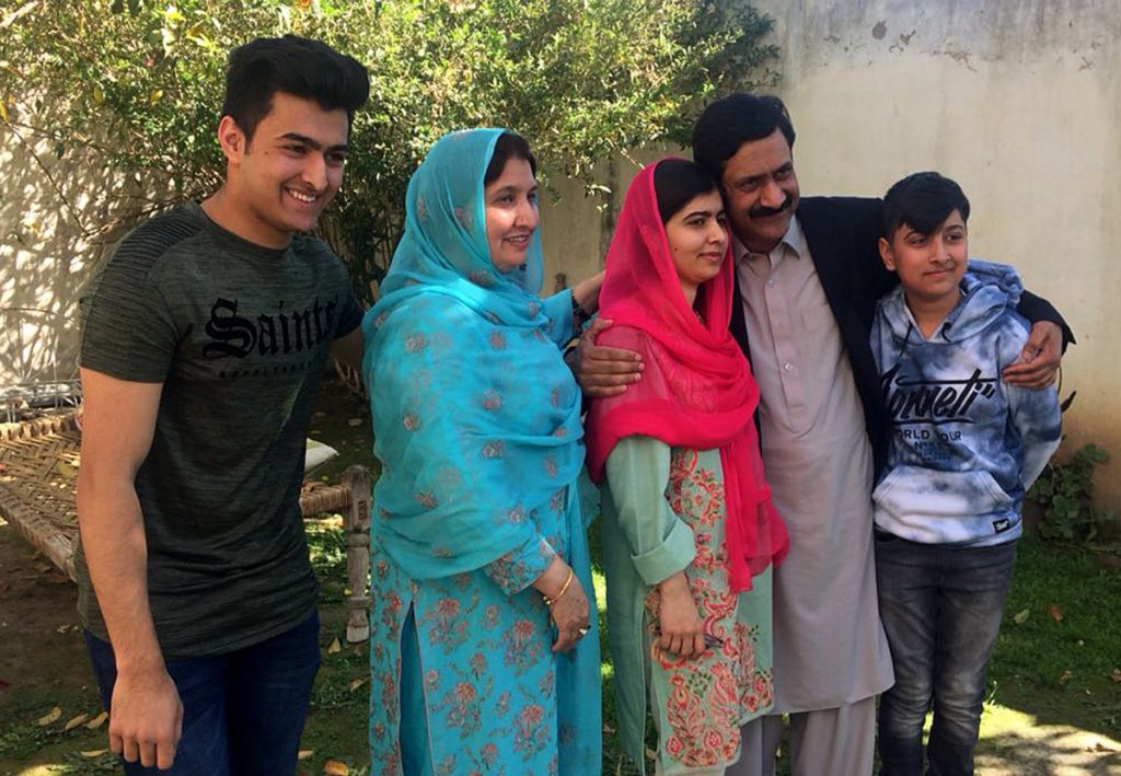 Malala Yousafzai, center, gathers with her family during a visit in March, 2018, to her hometown Mingora for the first time since a Taliban militant shot her there in 2012 for advocating girls' education.