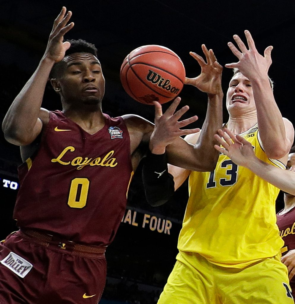 Loyola-Chicago's Donte Ingram, left, and Clayton Custer, right, battle for the rebound against Michigan's Moritz Wagner during the first half in the semifinals of the Final Four NCAA college basketball tournament, Saturday, March 31, 2018, in San Antonio. ()