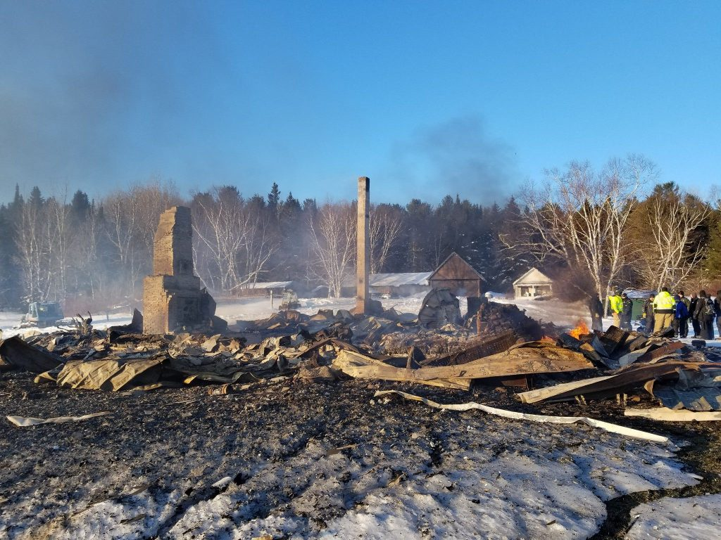 Officials look at the wreckage of the Chesuncook Lake House which started on fire early Saturday morning.