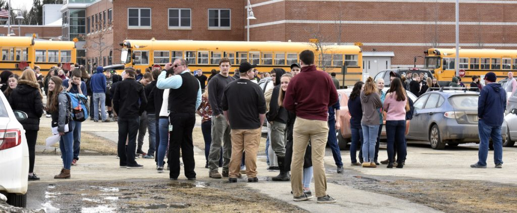 Students and staff stand outside the Mount View school complex in Thorndike as firefighters, police and ambulances responded to reports of a chemical leak on Wednesday that turned out to be pepper spray.