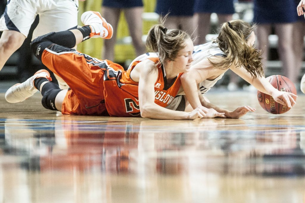 Winslow's Maeghan Bernard, left, battles for a loose ball with Presque Isle's Emily Wheaton during the Class B North championship game Saturday at the Cross Insurance Center in Bangor.