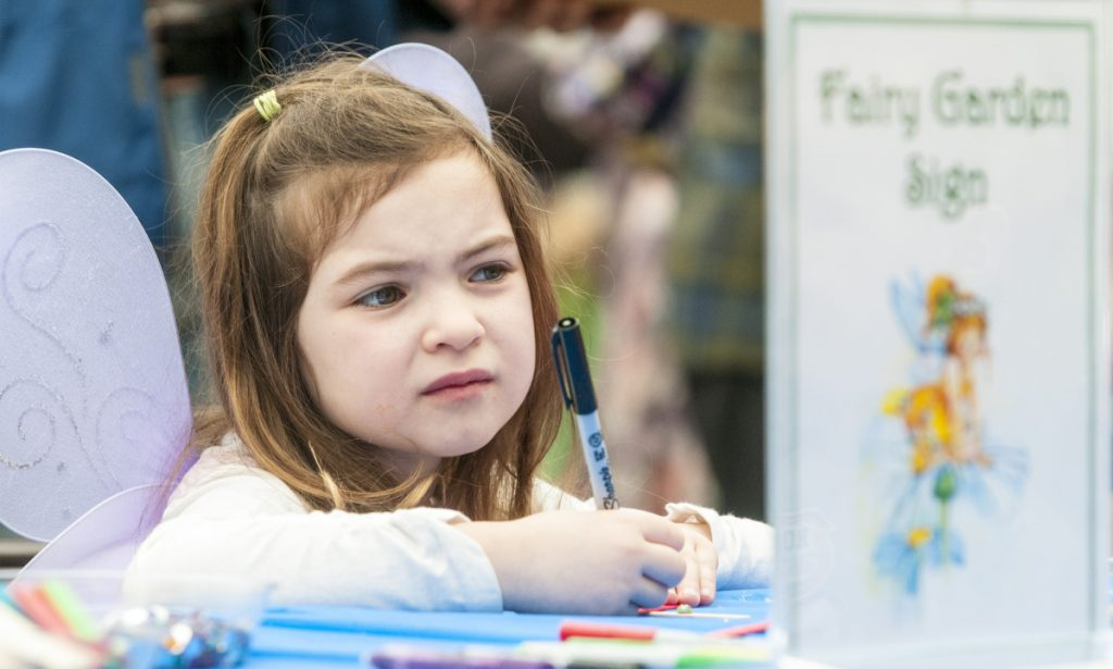 "Evelyn Robitaille, 5, of Greene, looks up on Saturday to check the spelling of ""Fairy Garden"" on the sign she's making out of popsicle sticks during the Annual Fairy Festival at Longfellow's Greenhouses in Manchester."