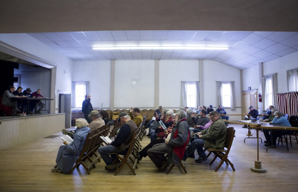 Cornville residents raise their hands to vote on a motion Saturday during Town Meeting at the Cornville Town Hall.
