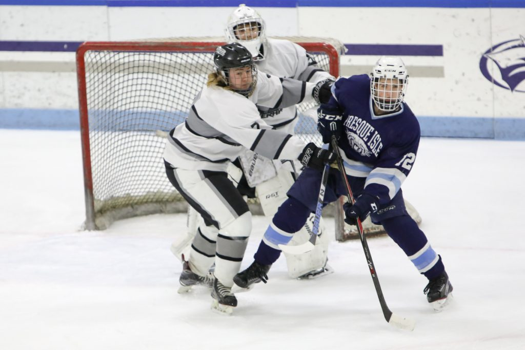 Kennebec's Nicholas West, left, defends goalie Bryce Gunzinger against Presque Isle's Bailey York during a Class B North semifinal game Saturday at Colby College.