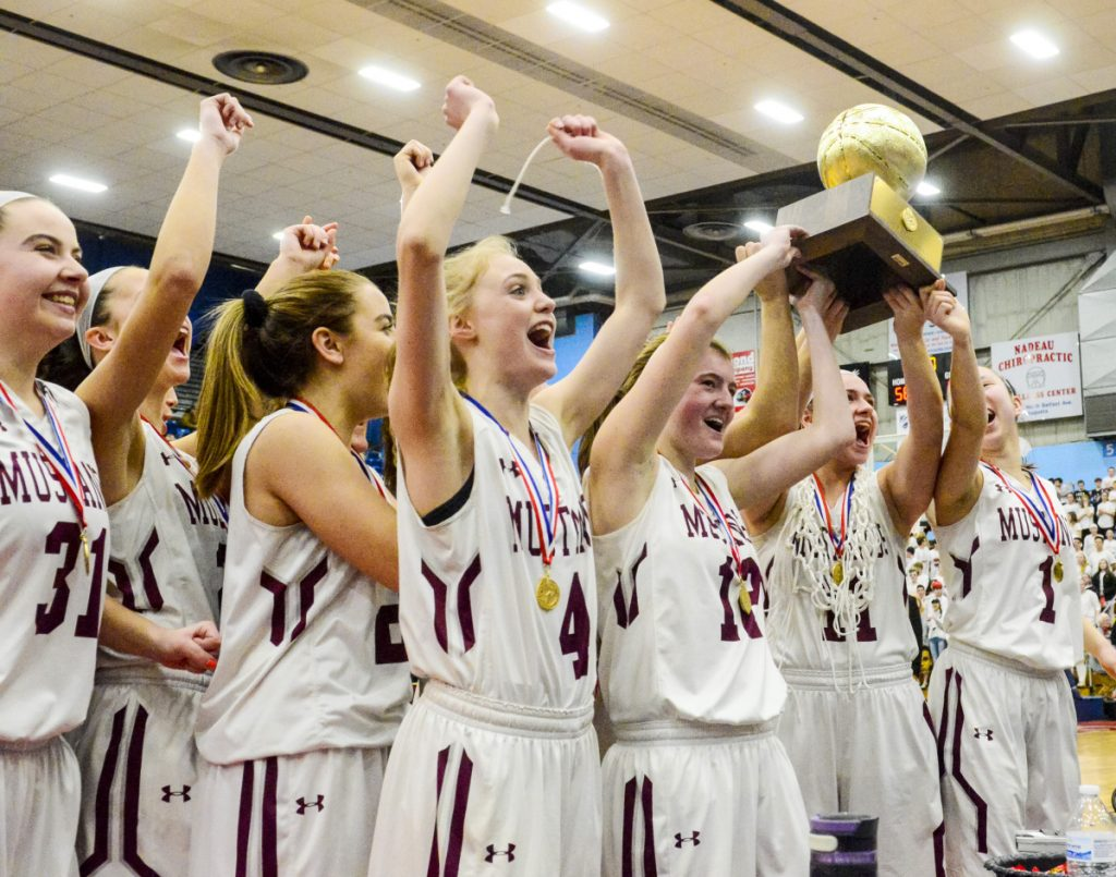 The Monmouth Academy Mustangs celebrate with Gold Ball after beating Houlton to win the Class C state championship game Saturday at the Augusta Civic Center.