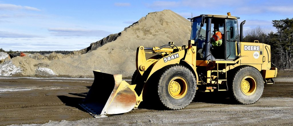 Moe Labbe, of the Winslow Public Works Department, smooths ruts Tuesday near the town sand pile after loading trucks for a snowstorm that is forecast to begin late Wednesday and last through Thursday.