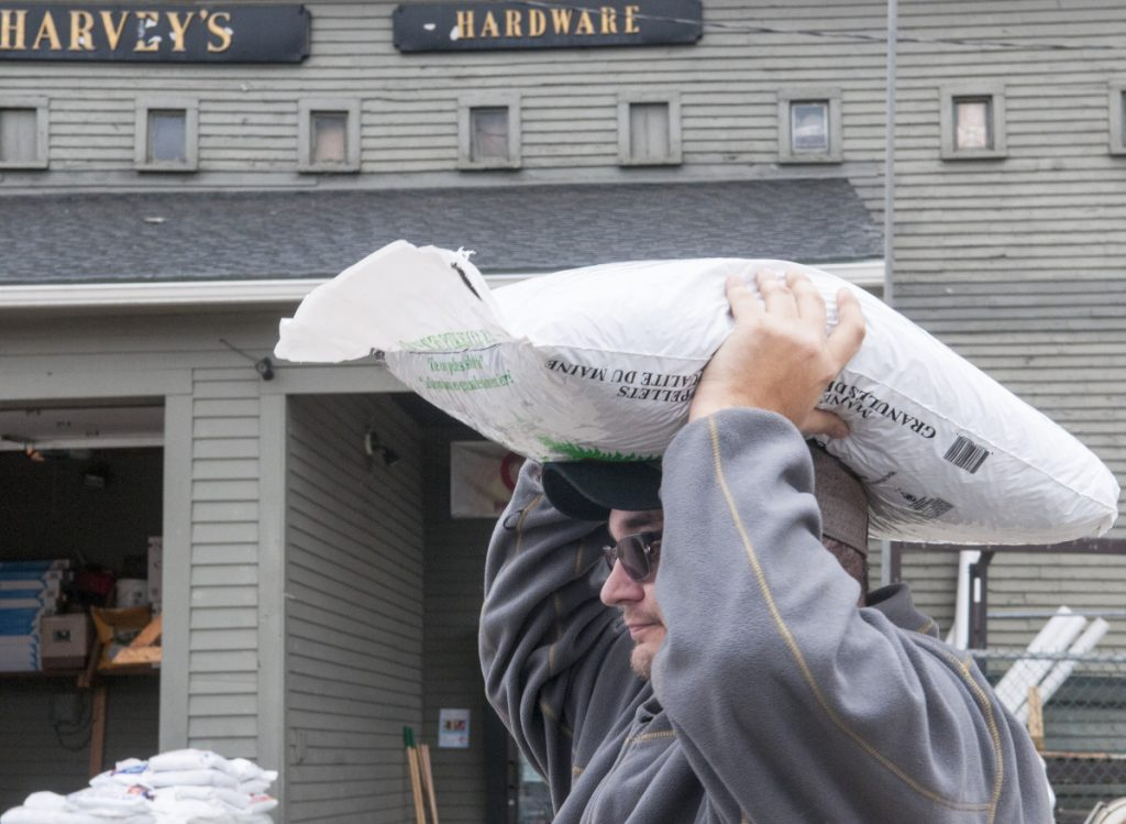 Liam Crocker, of Randolph, carries a bag of wood pellets on his head to a friend's car on Tuesday at Harvey Hardware in Gardiner, ahead of a snowstorm forecast for Wednesday night into Thursday.