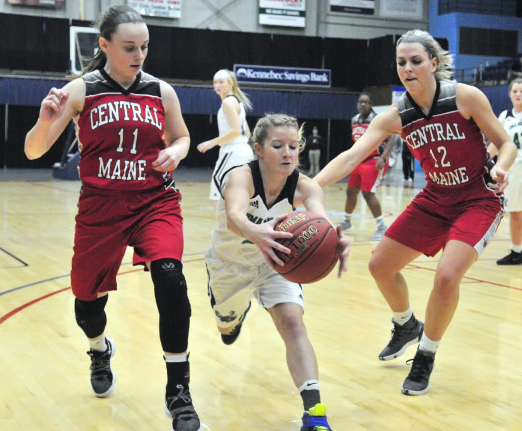 UMA's Emily Billings, center, grabs the ball before it goes out of bounds between Central Maine Community College's Kristina Blais, left, and Brooke Reynolds during a game earlier this season at the Augusta Civic Center.