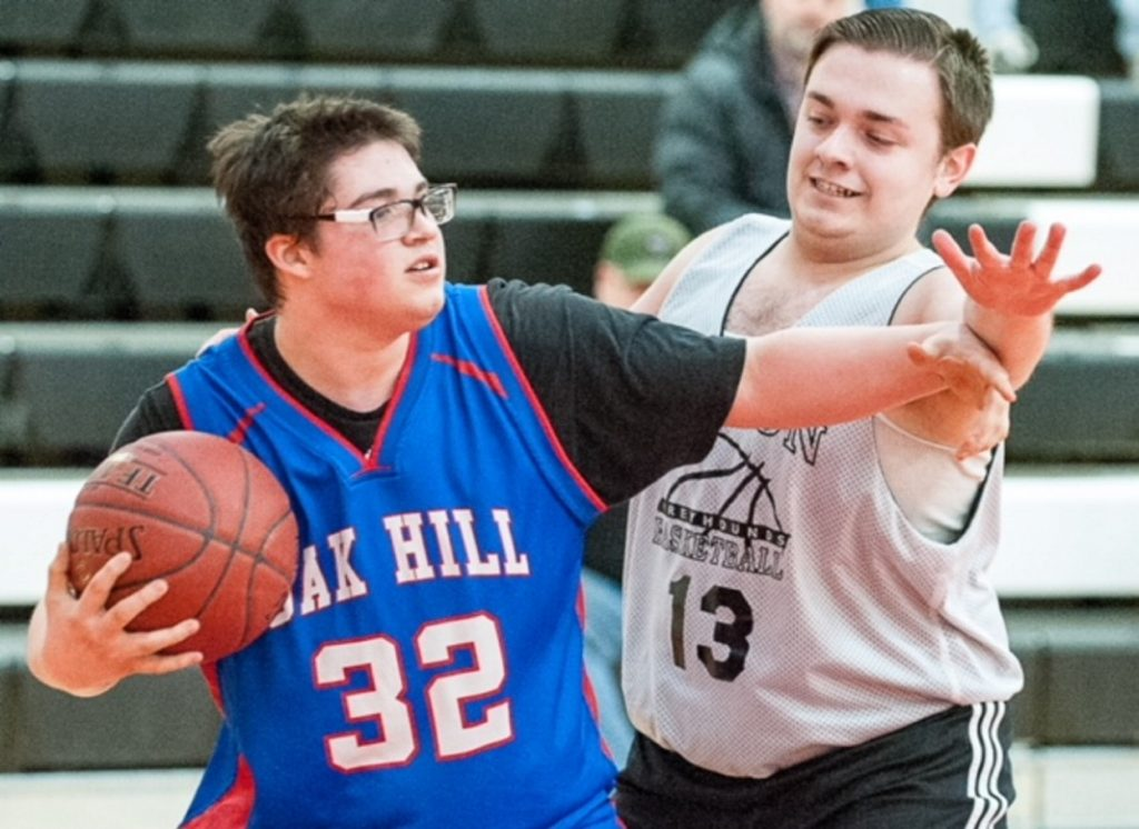 Lisbon's Dawson Martel, right, defends against Oak Hill's Tommy Grayson during the first half of Tuesday afternoon's Unified Basketball game in Lisbon.