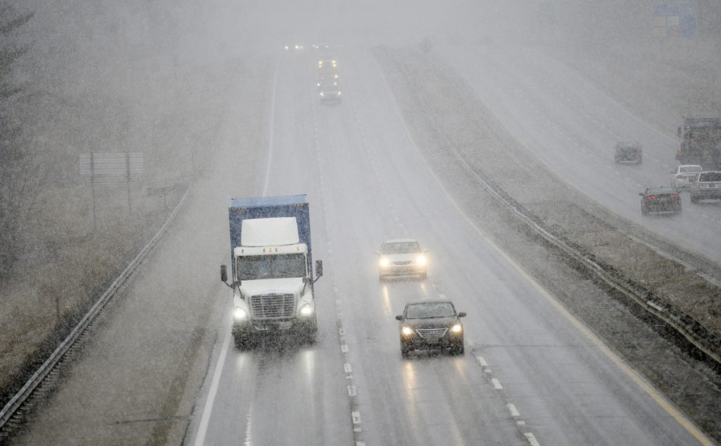 Vehicles make their way south on the Maine Turnpike as snow begins to fall Wednesday in Saco.