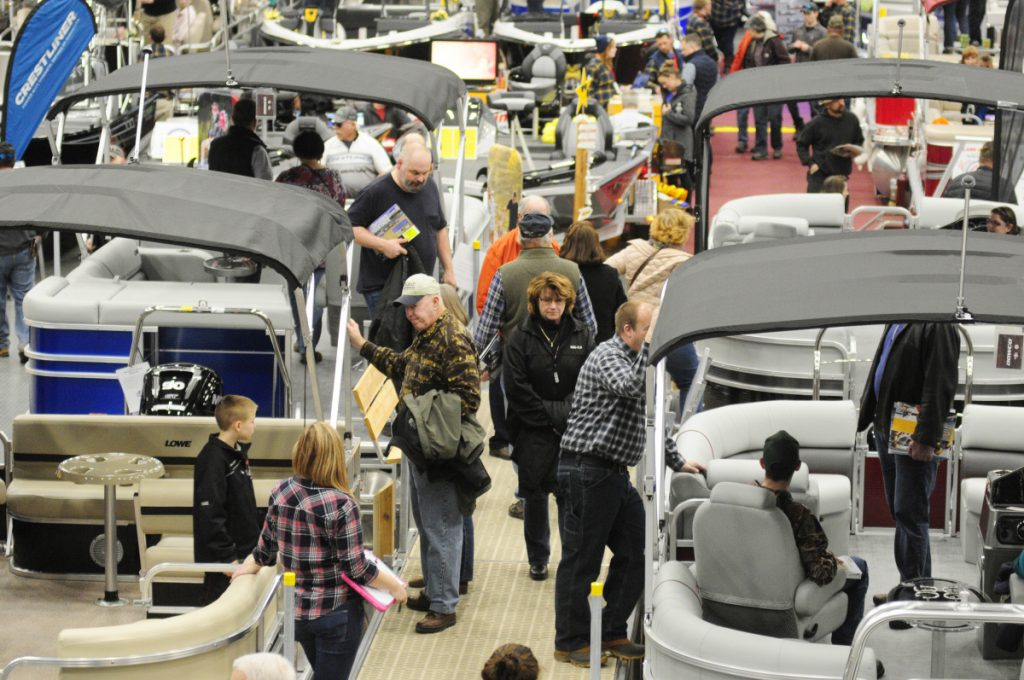People look over the boats on display Saturday during the Augusta Boat Show in the Paul G. Poulin Auditorium of the Augusta Civic Center.