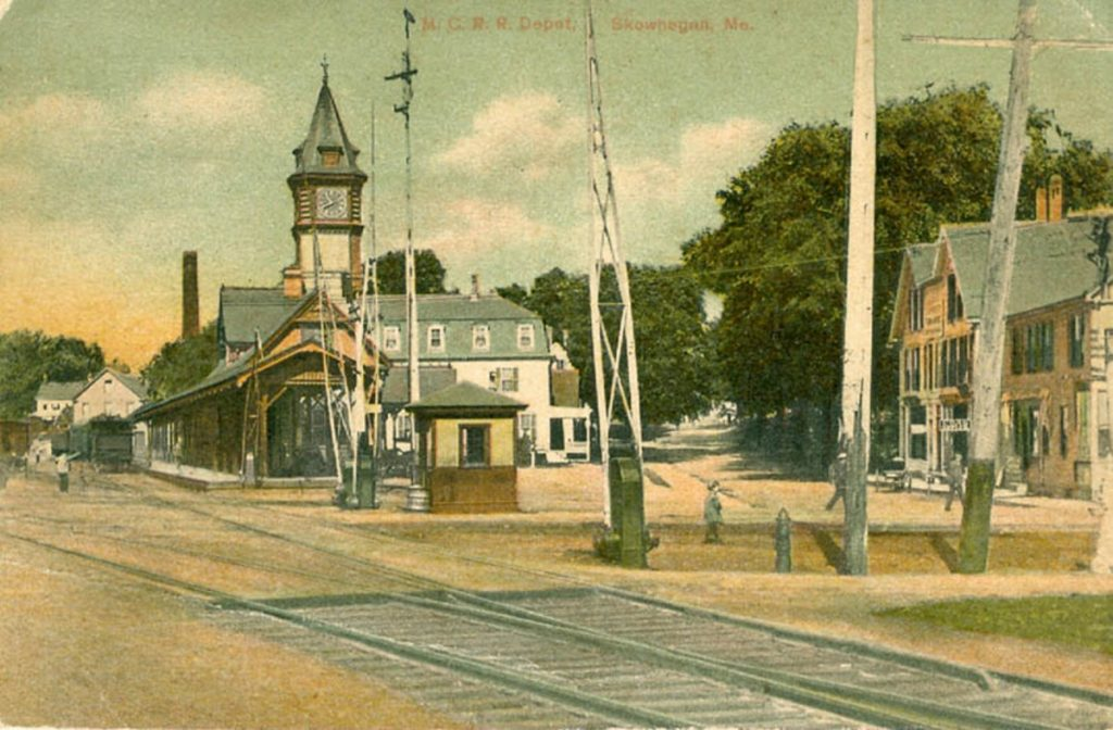 The Kennebec Valley Inn, originally the Maine Central Railroad Hotel, stands in the background of the train station with a clock tower, about 1905, in downtown Skowhegan.