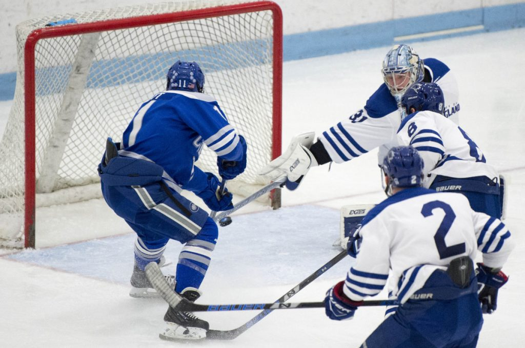 Colby College's Kienan Scott (11) scores a goal on University of New England goalie Tate Sproxton (31) in the second period Saturday in at the Alfond Youth Forum in Biddeford.