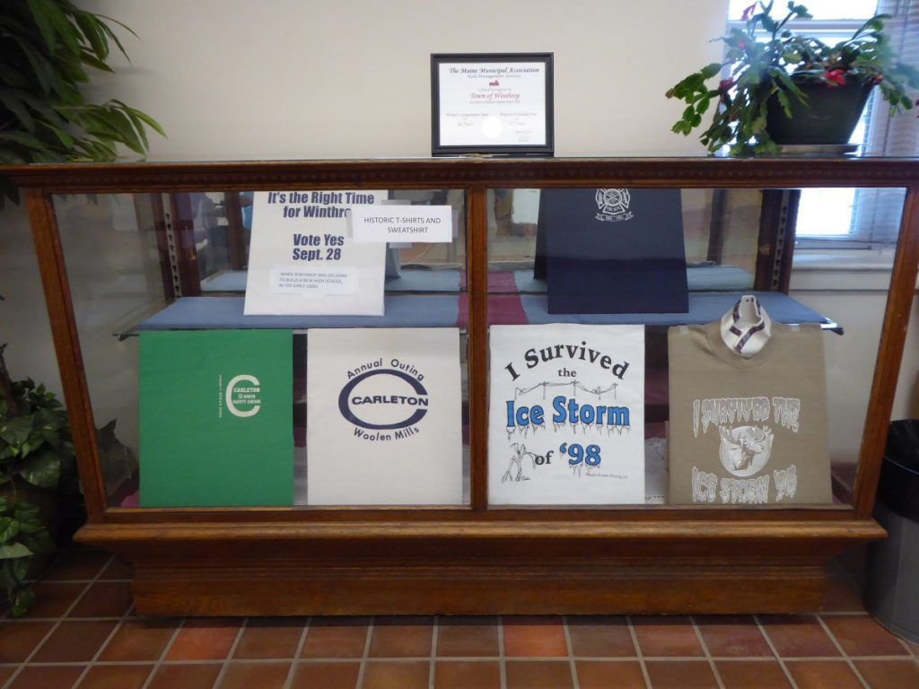 The display case in the Winthrop town clerk's room now features five historic T-shirts and a sweatshirt that refer to events in Winthrop's past.