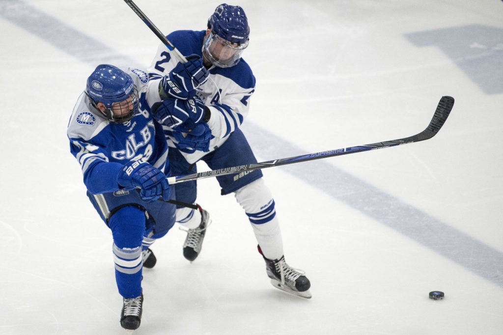 Colby's Phil Klitorinos, left, is checked by University of New England's Ian Rodden during an NCAA first round game last Saturday in Biddeford.
