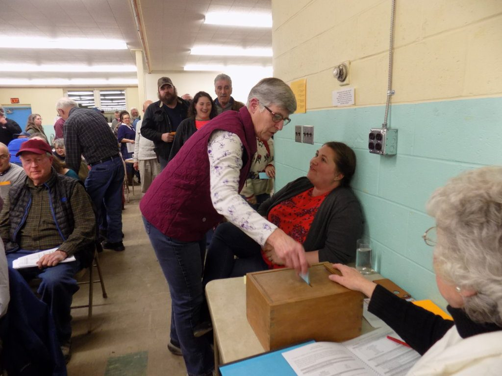 Anne Lambert casts her ballot Monday night at the Chesterville Town Meeting as Glenda Barker oversees the ballot box.