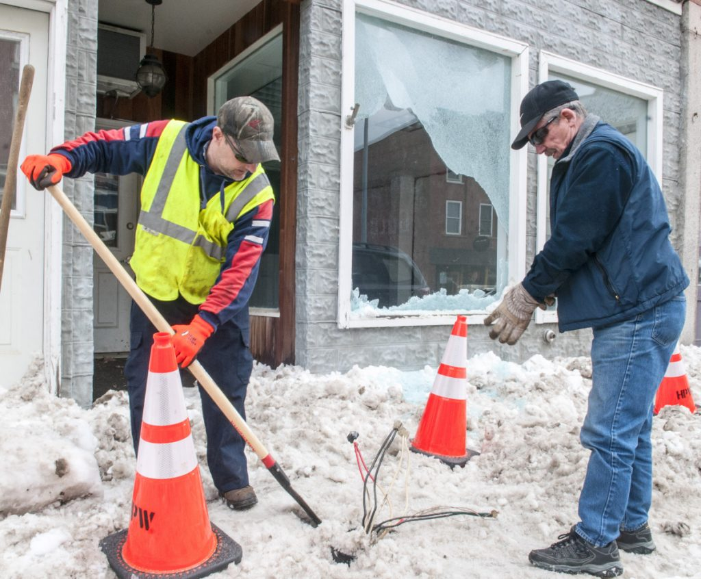 Todd Talon, left, of the Hallowell Public Works Department, scrapes snow away from the base of a broken light pole as Dick McGibney, of Dick's Electrical Service, prepares to wrap up wires Thursday. They were cleaning up after a tractor-trailer truck hit the streetlight and broke a window at 108 Water St. in downtown Hallowell.