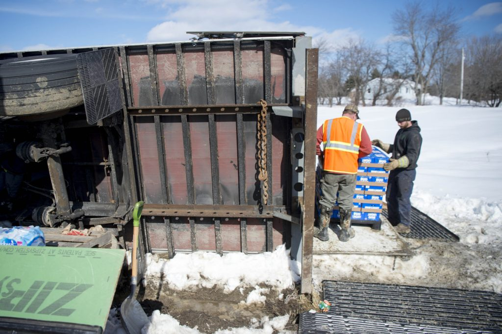 Crews carefully stack a tractor-trailer's payload of beer on pallets for transfer to another truck Friday after the first one rolled over on Trafton Road in Waterville when it hit a soft area on the road's shoulder.