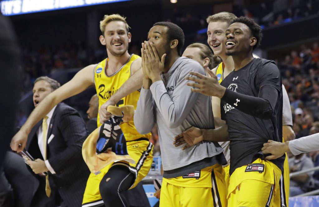 UMBC players celebrate a teammate's basket against Virginia during the second half of a first-round game in the NCAA tournament Friday night in Charlotte, North Carolina.