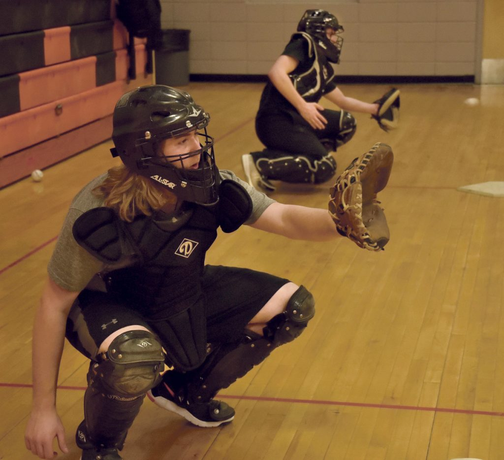 Winslow catchers Nick West, left, and Bryce Gunzinger get some work in Monday afternoon at the high school.
