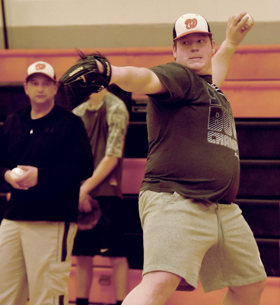 Winslow pitcher Cameron Winslow throws during practice for pitchers and catchers Monday afternoon. Assistant coach Kris Targett, left, observes.