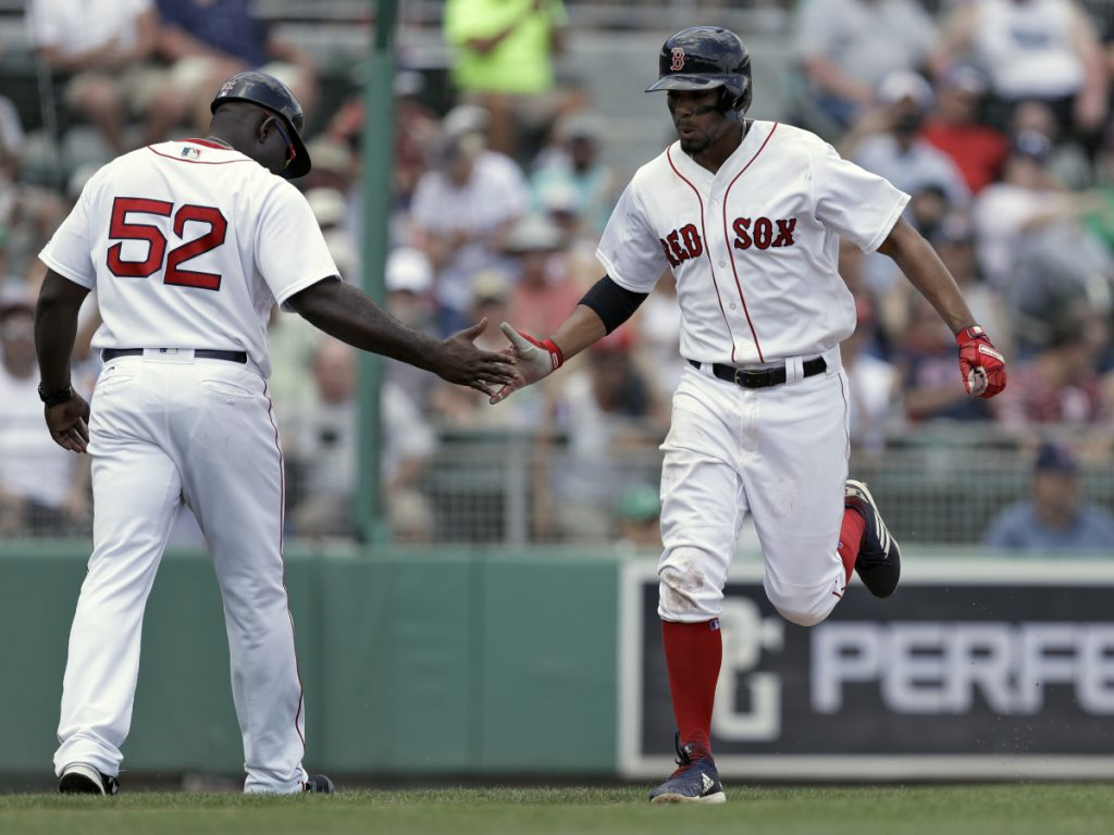 Boston Red Sox shortstop Xander Bogaerts celebrates his home run off Phillies pitcher Drew Hutchison with third base coach Carlos Febles (52) during the fourth inning Monday.