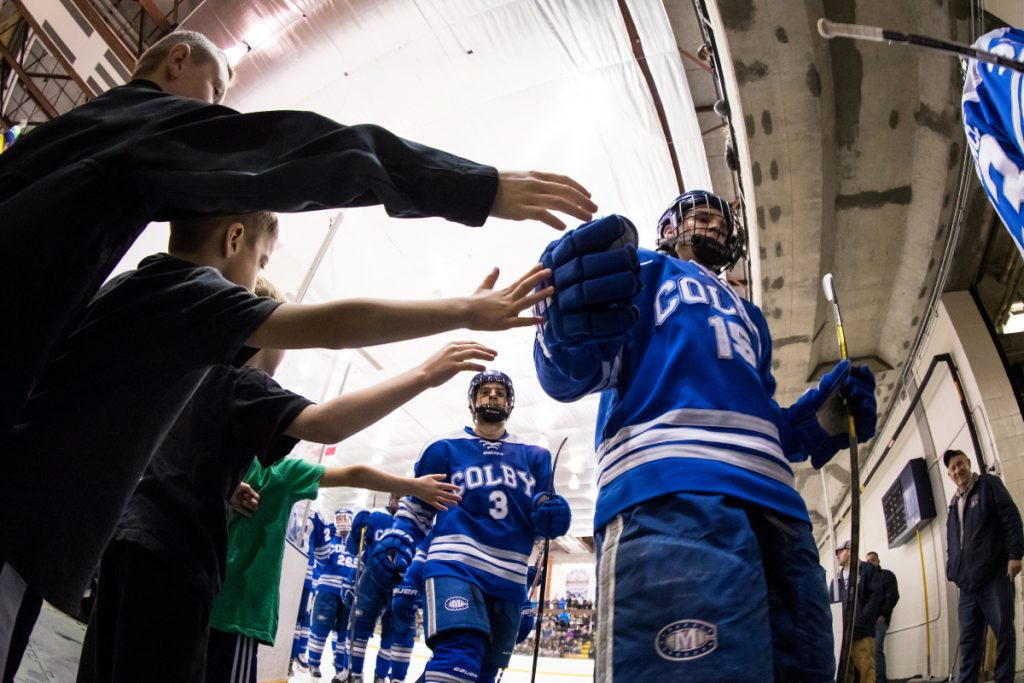 Young fans try to high-five Colby hockey players, including Mark Leprine (3) and Griffin Fadden (front) during an intermission of an NCAA Division III quarterfinal against SUNY Geneseo last March. Colby opens the new season this weekend at home with a pair of games.