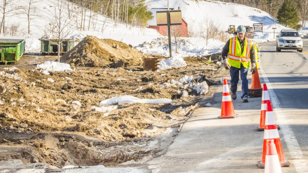 A worker from Enviro lines up traffic cones along Route 27 in Belgrade on Monday after a gasoline spill around Christy's Country Store in Belgrade.