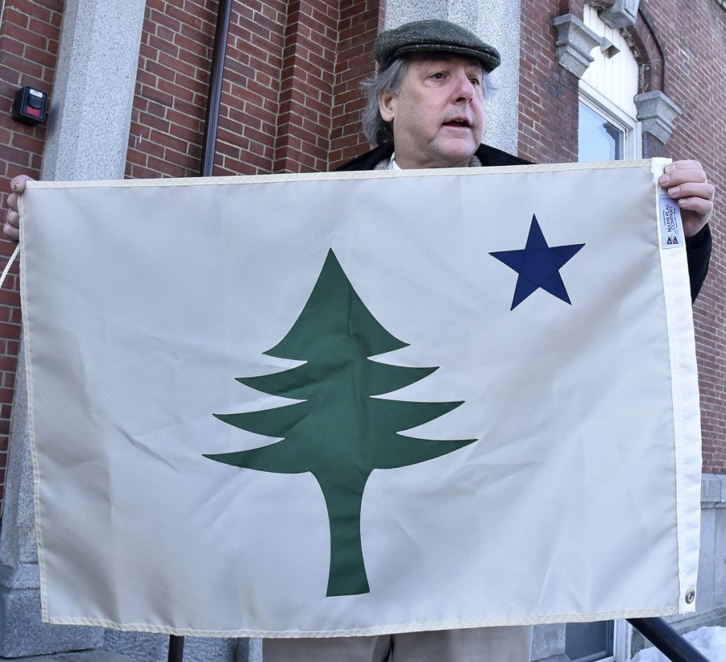 Somerset County Commissioner Robert Sezak holds a replica of the original state of Maine flag used from 1901 through 1909 before the flag was hoisted up a flagpole at the Somerset Superior Courthouse in Skowhegan on Wednesday.