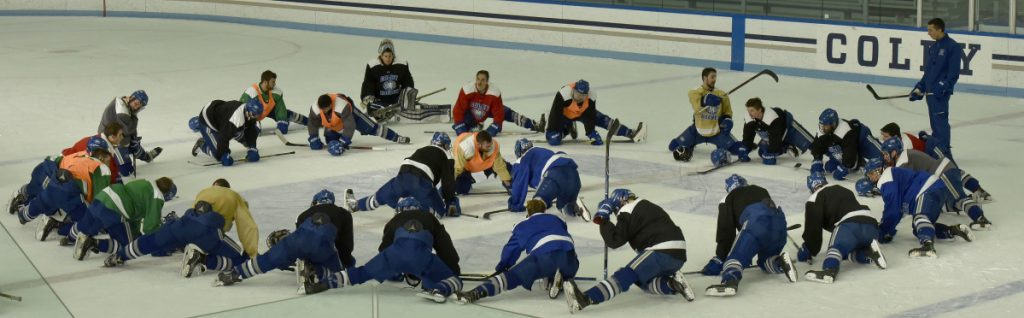 Colby College assistant hockey coach Chris Hall leads the team in stretches during practice Tuesday in Waterville.