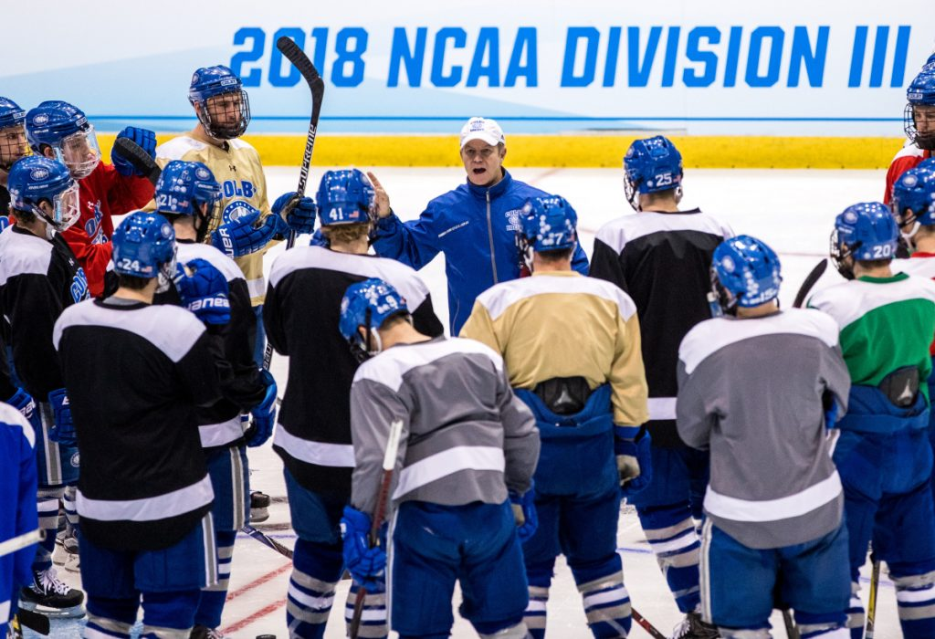 Colby men's hockey coach Blaise MacDonald, front left, talks to his team during practice Thursday afternoon at Herb Brooks Arena in Lake Placid, New York. The Mules will play St. Norbert College in an NCAA Division III Frozen Four game Friday at 6:30 p.m.