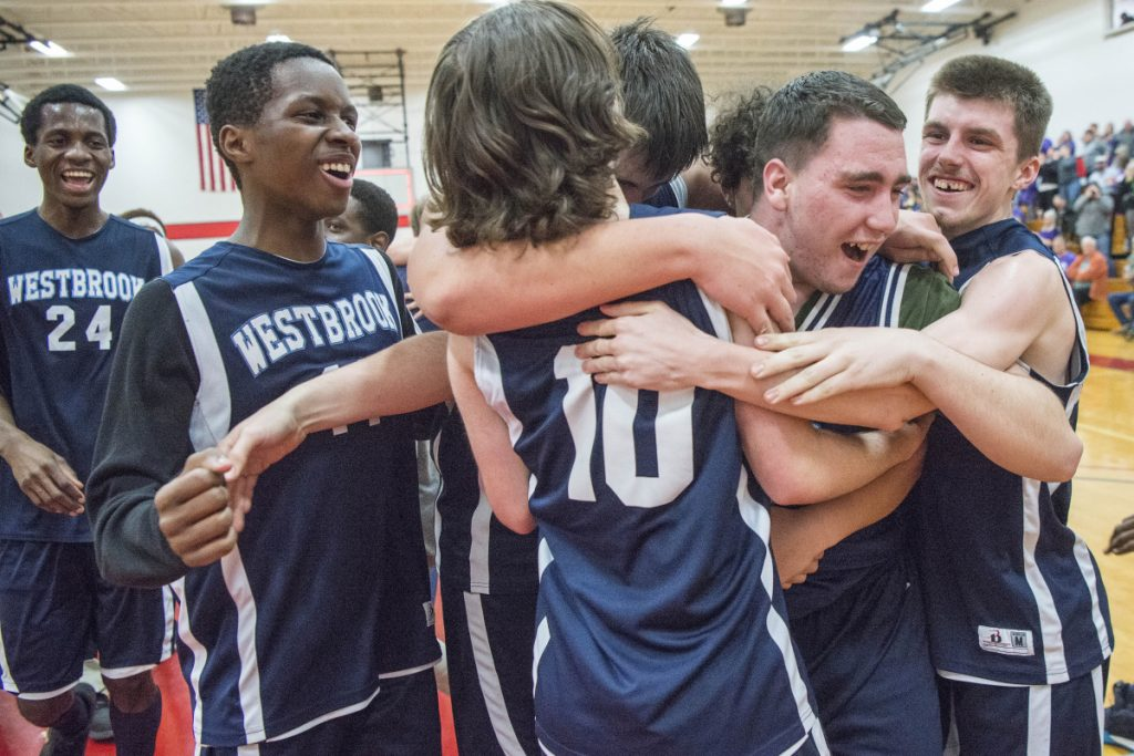 Members of the Westbrok High School unified basketball team celebrate after they beat Hampden Academy in the state final Thursday night at Thomas College in Waterville.