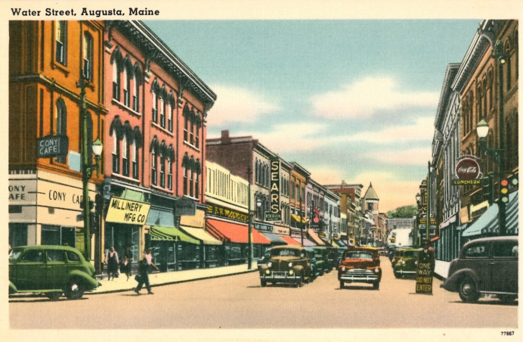 This mid-20th-century postcard shows one-way traffic on Water Street looking south from Bridge Street in downtown Augusta.