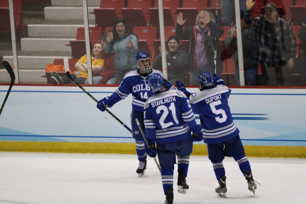Colby players Cam MacDonald (14), Thomas Stahlhuth, Dan Dupont celebrate after the Mules pulled to within 3-2 against St. Norbert College during a Division III Frozen Four game Friday in Lake Placid.