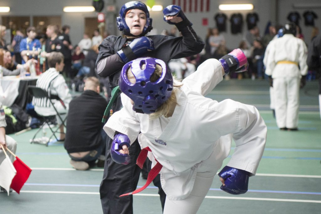 Staff photo by Michael G. Seamans   Lauren Heathcote, foreground, delivers a kick to Skyeler Poolis at the Battle of Maine Martial Arts tournament Saturday at Thomas College in Waterville.