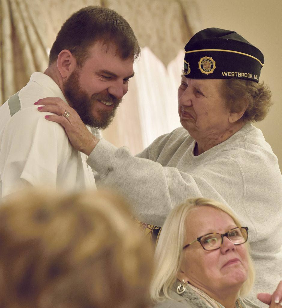"Veterans advocate Travis Mills gets a hug from Mary ""Dottie"" McGuirk, a 20-year Air Force nurse who served in Southeast Asia during the Vietnam War, during a National Vietnam Veterans Day celebration Thursday in Waterville."