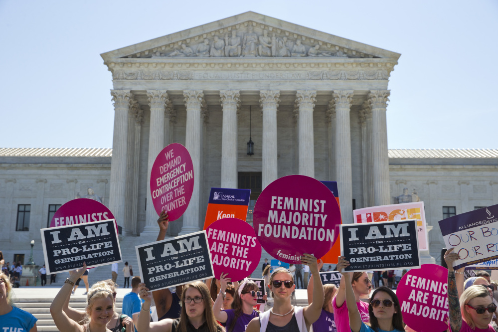 Demonstrators on both sides of the abortion issue stand in front of the Supreme Court in Washington, Monday, June 20, 2016, as the court announced several decisions.