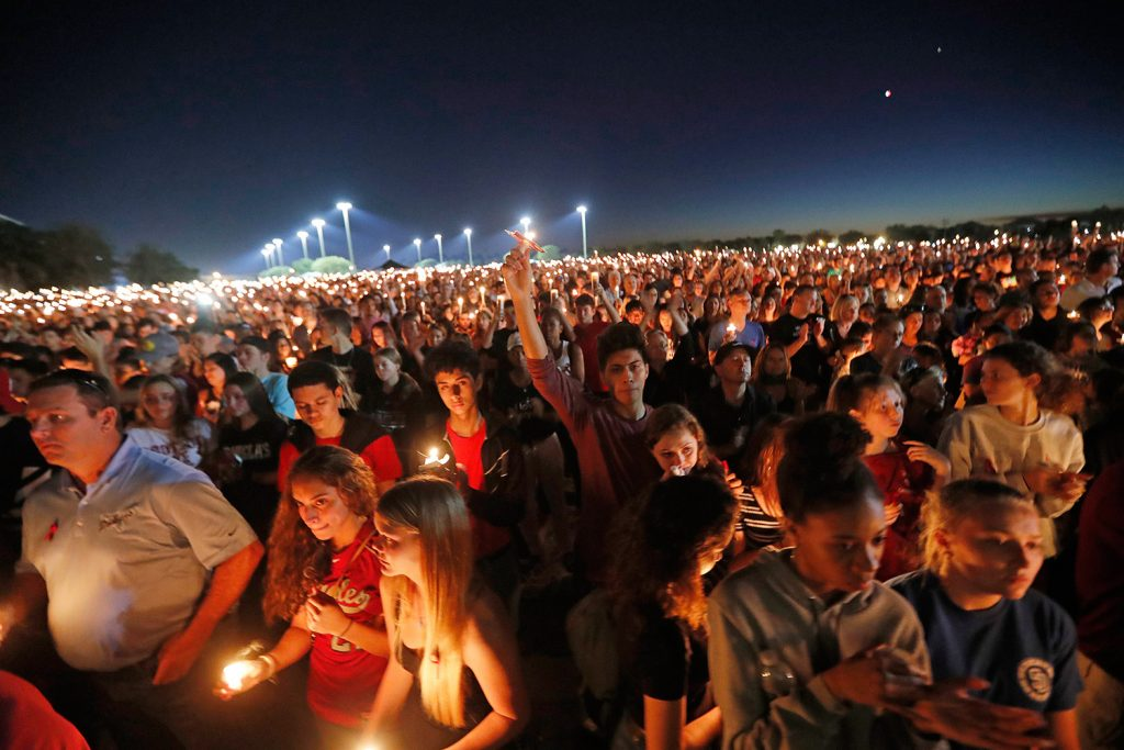 Hundreds hoist their candles during a vigil in Parkland, Fla., for the victims of a school shooting at Marjory Stoneman Douglas High School.