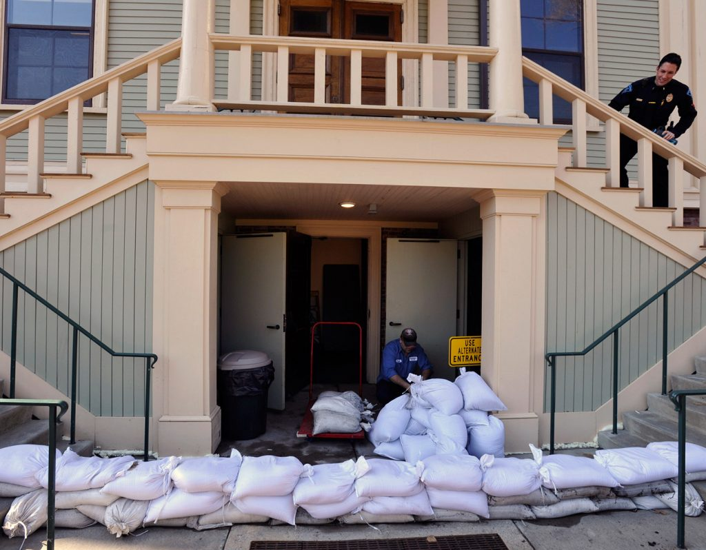 Paulo Andrade moves sand bags around the lower entrance to the town hall in Provincetown, Mass., on Thursday in preparation for the approaching storm.