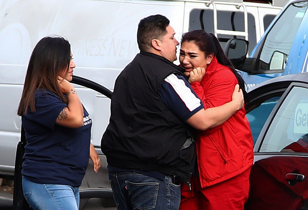 Fernando Juarez, center, embraces his sister Vanessa Flores at the Veterans Home of California on Friday. Flores, a caregiver at the facility, exchanged texts with family members while sheltering in place as a gunman took at least three people hostage at the largest veterans home in the United States.