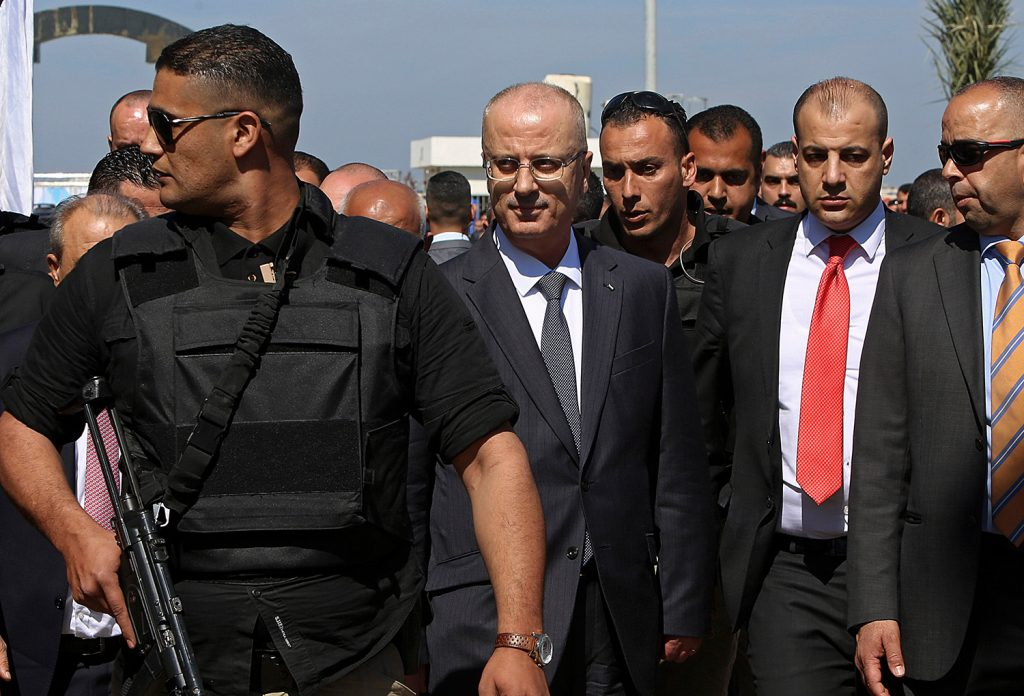 Palestinian Prime Minister Rami Hamdallah, center left, is surrounded by body guards Tuesday as he arrives for the opening ceremony for a long-awaited sewage plant project in the northern Gaza Strip. An explosion occurred as the convoy of the prime minister entered Gaza through the Erez crossing with Israel. The Fatah party of the prime minister called the explosion an assassination attempt and blamed Gaza militants.