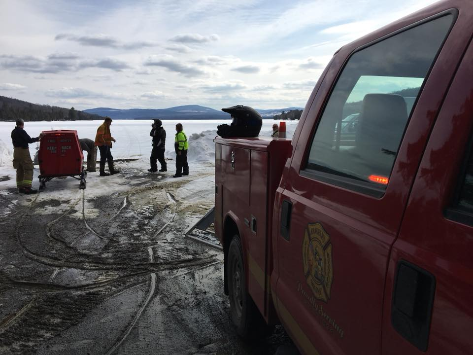 Members of the Rangeley Fire Rescue Department assist at a snowmobile accident on Rangeley Lake in Rangeley late Wednesday morning. It was the first of two crashes this week that injured snowmobilers who hit pressure ridges.
