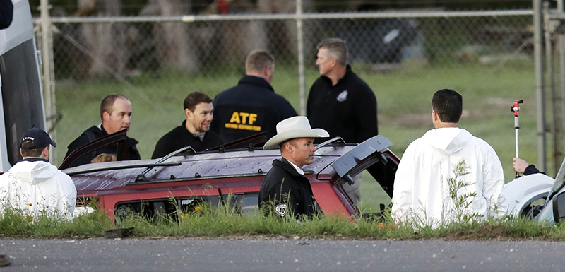 Officials investigate the scene where a suspect in a series of bombing attacks in Austin blew himself up as authorities closed in on Wednesday,  in Round Rock, Texas.
